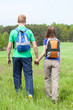 Couple holding hands and walking on a grass field