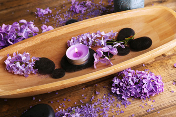 Composition with wooden bowl with water and lilac flowers,