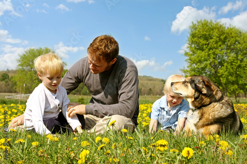 Father, Children, and Dog Relaxing in Flower Meadow