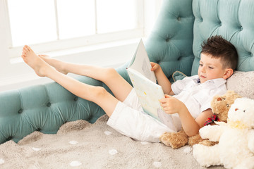 Young boy reading book lying down on couch at home