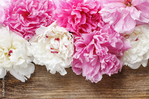 Stunning pink peonies, yellow carnations and roses on rustic