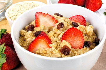 Close up of oatmeal cereal with strawberries and raisins