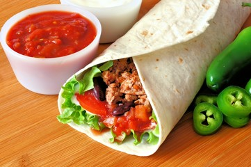 Burrito with meat and vegetables with salsa and peppers