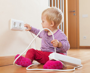 Toddler playing with extension cord