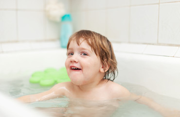 Happy two-year child bathes in bathtub