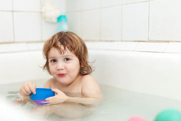 child bathes  in bath