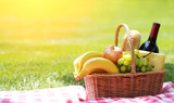 Fototapety Picnic basket with food on green grass
