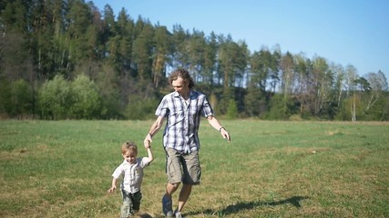 young father with son playing and running outdoors, slow motion