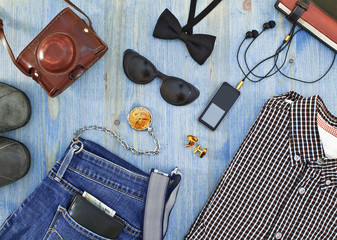 Set of men's clothing and accessories on blue wooden table.