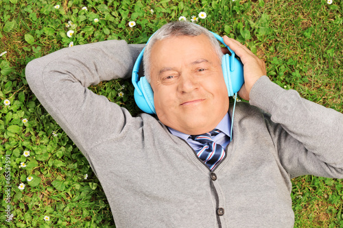 Mature man with headphones lying on grass