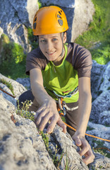 Smiling woman, rock climber in yellow helmet during sunset.