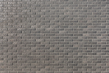 Wall from a dark brick with a pattern in a bright sunny day as a