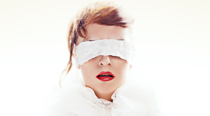 Portrait of attractive woman blindfolded with white paper ribbon