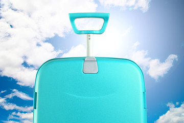 turquoise trolley suitcase on bright sky
