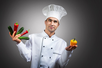 Humorous portrait of a chef with vegetables in his hands