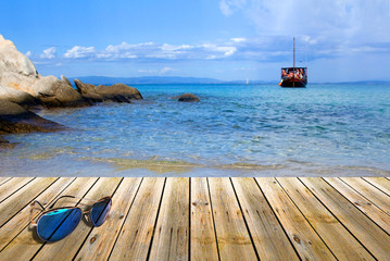 Wood pier with sunglasses,beside tropical Greece beach