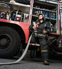 Firefighter near truck with equipment with water hose