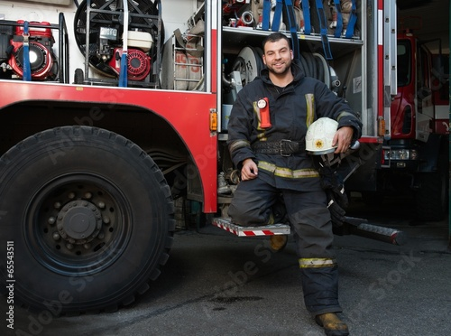 Cheerful firefighter near truck with equipment - 65543511