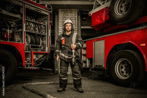 Firefighter near truck with equipment with water hose  - 65543531
