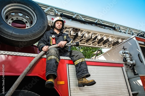 Firefighter sitting on a firefighting truck with water hose - 65543569