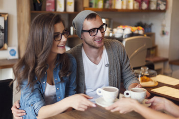 Fashion couple receiving cup of coffee from waitress