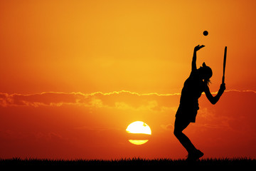 girl playing tennis at sunset