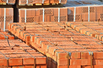 Stack of orange clay silicate brick on construction site