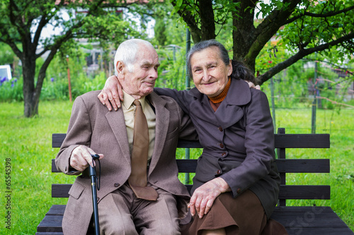 Leinwanddruck Bild Cute 80 plus year old married couple in their garden.