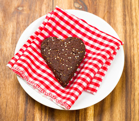 Close-up of dark chocolate chia seed love heart cookie