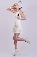 Beautiful girl posing in white dress in the studio