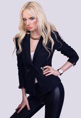 Fashionable blonde girl posing on grey background