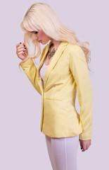 Fashionable blonde model posing on grey background