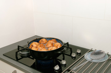 Typical Dutch oliebollen in hot oil