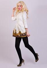 Beautiful blonde girl posing in elegant dress in the studio