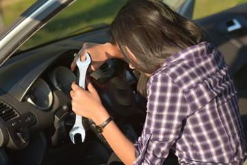 Beautiful woman holding Hand wrench near broken car