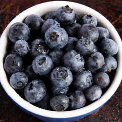 Blueberries in blue bowl on brown background