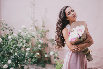 beautiful girl with a bouquet of peonies