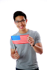 Cheerful asian man holding flag of USA over white background