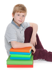 Serious young boy near books