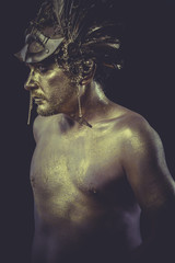 Bronze man with body painted gold feather mask and steel sword
