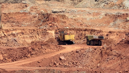 Mining dump trucks and excavators in the open pit mine