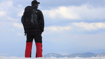 Man at the snowy mountain peak looking at beautiful view