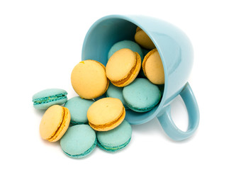 orange and blue macarons in a blue cup