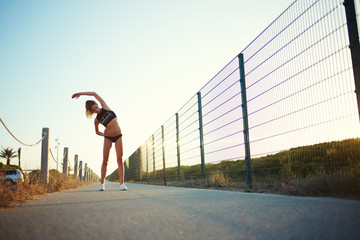 Athletic sports girl doing stretching exercises at sunset