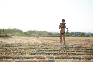 Beautiful athletic girl runs across the field at sunset