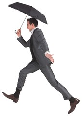 Businessman jumping holding an umbrella