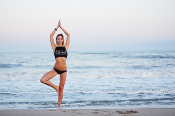 Beautiful  young girl engage yoga on the beach