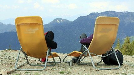 Rear view of a couple couple relaxing in the mountains