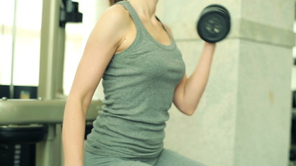 Young fit woman exercising with dumbbels in the gym