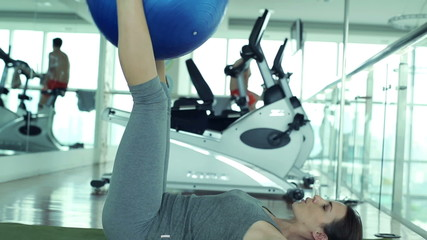 Young fit woman exercising with fitness ball in the gym